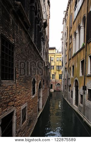 Venice Italy - September 22 2015: venetian canal narrow street serves as road for vessel transport between old terracotta yellow buildings shallow lagoon on townscape background vertical picture