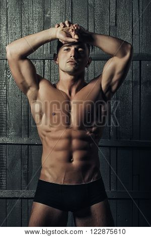Handsome sensual serious young boy brunet with muscular bare torso strong abdominal and biceps muscles looking straight in black male trendy underpants posing on gray wooden background vertical