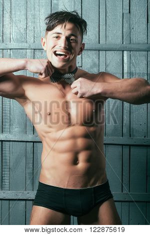 Happy charming sexual delightful young man athlete smiling brunette with cool abdominal shirtless torso in black underpants touching bow on neck posing on wooden background closeup studio vertical