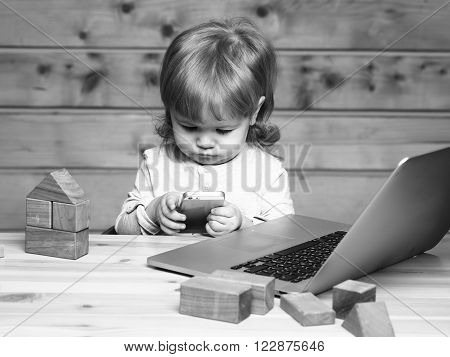 Cute funny little baby boy with long blonde curly hair playing on computer and mobile phone near toy building blocks indoor on wooden background, horizontal picture
