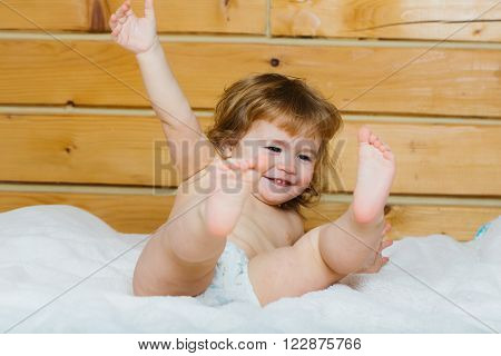 Cute happy beautiful smiling playful child boy with wet hair sitting in hothouse bath white fluffy towel naked indoor on wooden background, horizontal picture