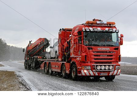 SALO, FINLAND - MARCH 20, 2016: Truck and car are being towed by a heavy duty tow truck in snowfall. Heavy duty towing requires special skills and equipment.