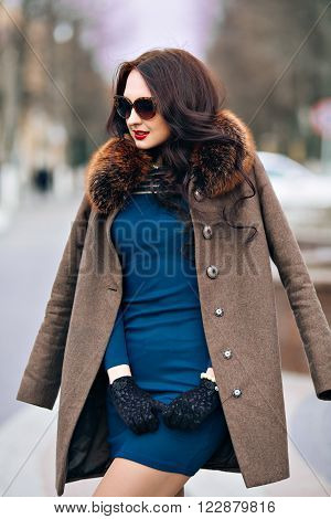 fashion Outdoors Sexy glamor young woman with chic long dark hair beautiful young brunette girl wearing stylish sunglasses, trendy green dress, luxurious fur coats and gloves fashion makeup posing in autumn park