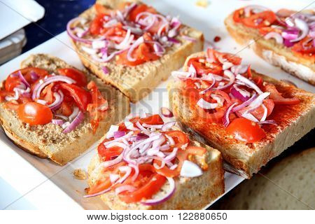 Fast food as bread and dripping with tomatoes and onions. Swallow depth of fields