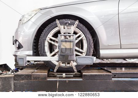 Closeup Of Tire Clamped With Aligner Undergoing Auto Wheel Alignment