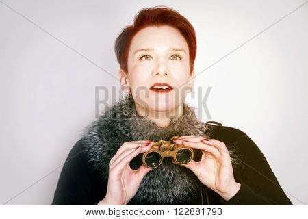 red-haired woman looking through binoculars and looks astonished