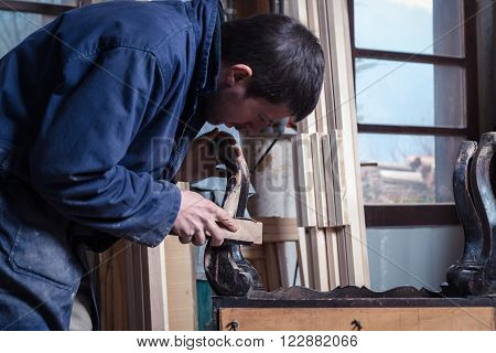 Portrait of Carpenter restoring Wooden Furniture with sandpaper in his workshop.
