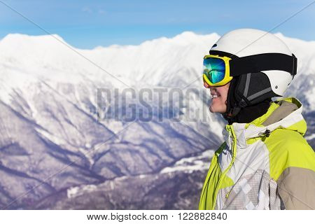 Close profile portrait of a woman wearing ski mask and helmet over mountains