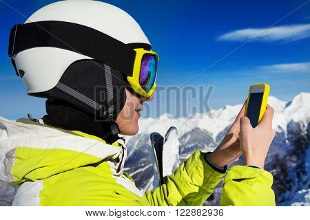 Young skier woman look up something in the phone wearing ski mask and helmet view over the shoulder