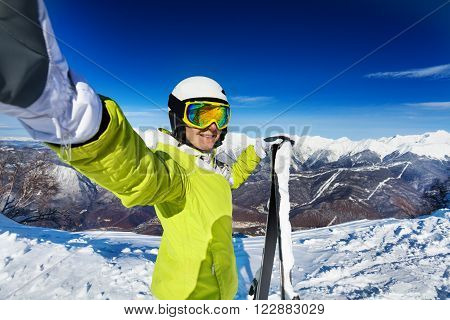 Woman taking selfie with stretched hand wearing ski mask and helmet and holding ski in high mountain