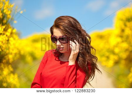 outdoor photo of beautiful sexy girl in elegant dress posing in summer field of red poppies