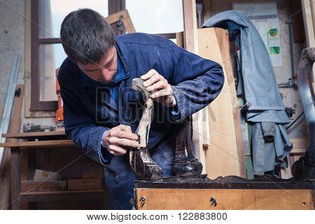 Portrait of Carpenter restoring Wooden Furniture with sandpaper in his workshop.