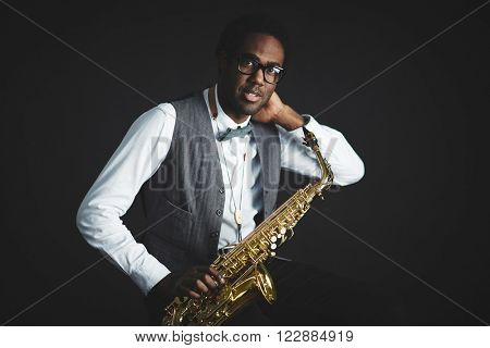 Portrait of young saxophonist with his instrument
