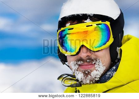Close portrait of skier man in ski mask and helmet with snow on beard