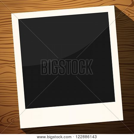 Black instant photo with frame on a wooden surface.