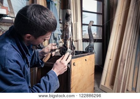 Portrait of Carpenter restoring Wooden Furniture with plaster and putty Knife in his workshop.