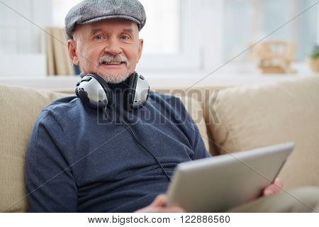 Portrait of senior man with headphone using touchpad