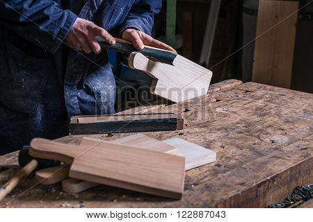 Close up of Carpenter's Hands sanding piece of Wooden Cutting Board with sandpaper in his workshop.