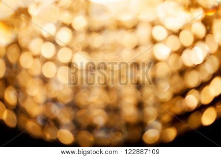 Golden Bokeh Lights. Blurred Crystal Chandelier Background. Darkness And Light Concept. Soft Abstrac