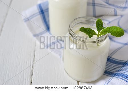 natural yogurt in glass jar white background
