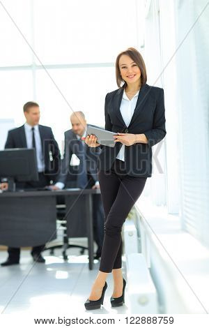 happy young woman using digital tablet in office