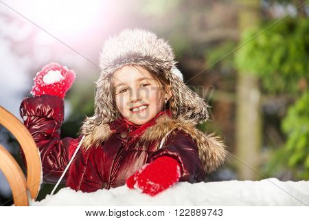 Smiling girl having fun with snowball fight at the sunny winter day
