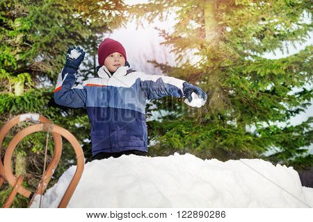 Boy throwing snowballs in his winter wear on the green spruces background