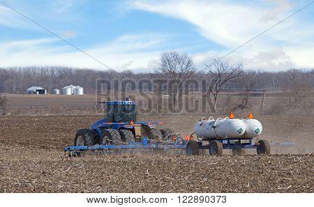 Farm tractor pulling anhydrous ammonia tanks fertilizing farmland