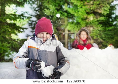 Two happy friends boy and girl playing at the snowballs