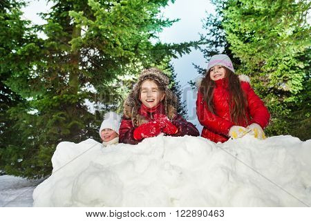 Tree Caucasian laughing girls playing snowballs at sunny winter day