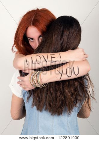 red-haired girl hugging her friend in her arms the inscription I love you.