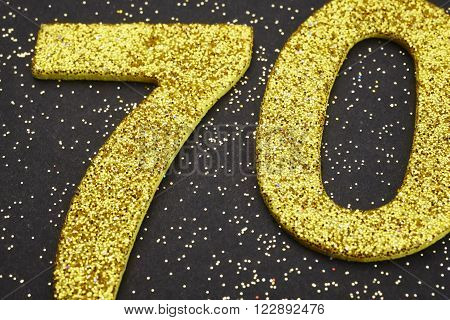 Number seventy golden color over a black background. Anniversary. Horizontal