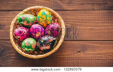 Beautiful Painted Colorful Easter Eggs In A Wickerwork Basket On Old Brown Wooden Background