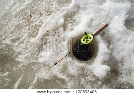 During winter fishing rod lying on the ice near the hole