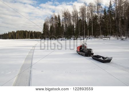 snowmobile with a trailer is on the lake around the snowy forest in sunny weather