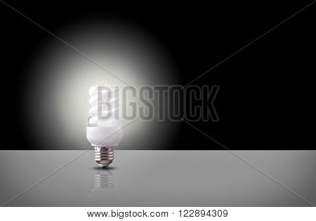 One espiral light bulb on white table with black background. Front view. Horizontal composition