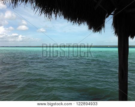 The multi-colored waters of Laguna Bacalar Mexico as seen from an indigenous-styled thatched wooden dock.