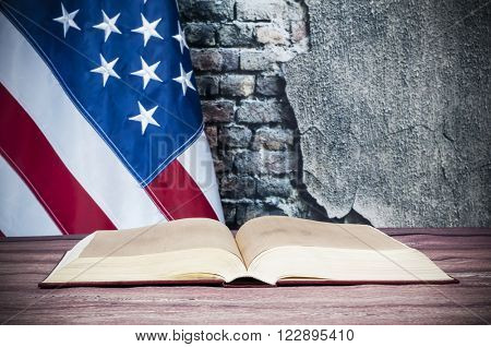 Opened book on a background of the USA flag