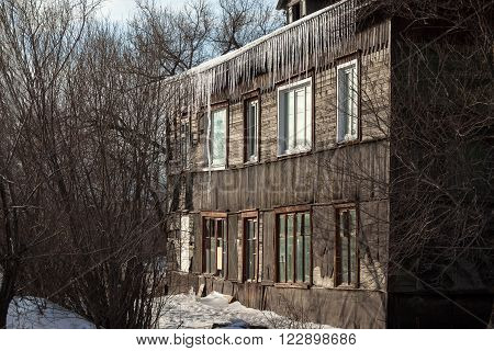 Icicles hanging down from the roof of an old house