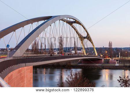 FRANKFURT GERMANY - MAR 14: Osthafen bridge over the Main river illuminated at dusk. March 14 2016 in Frankfurt Main Germany