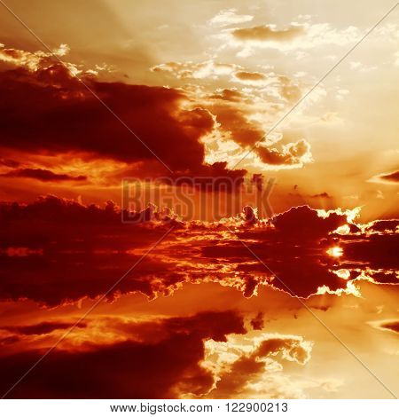 Red sunset over the sea rich in dark clouds rays of light