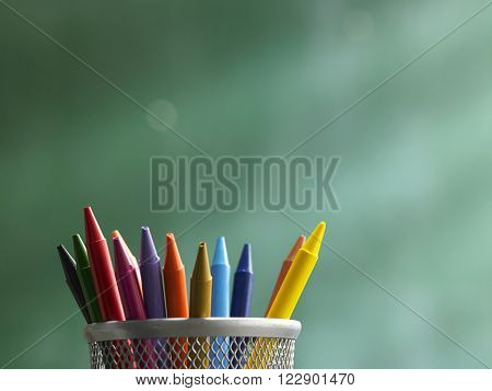 Wax crayons in front of blackboard ,concept  stand out from the crowd