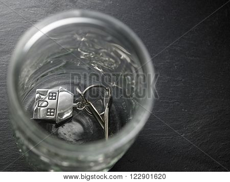 empty saving glass container with house shaped key chain