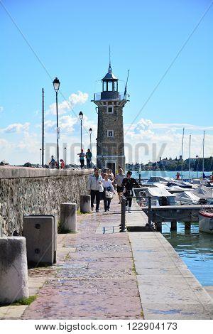 DESENZANO ITALY - 09.17.2013: Desenzano town Italy Garda Lake lighthouse coastline landscape