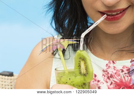 Young female drinking kiwi smoothie by using a drinking straw