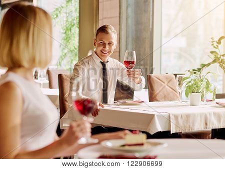 Unexpected meeting. Handsome young man is looking at beautiful woman while sitting separately in the restaurant.