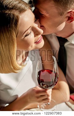 Love confession. Shot of handsome man standing close to woman with glass of wine and whispering in her ear.