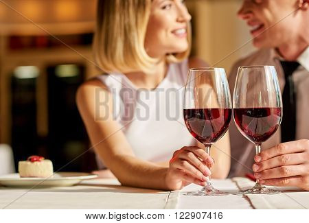 Romantic evening. Nice smiling couple looking at each other and enjoying time while holding glasses of wine in the restaurant.