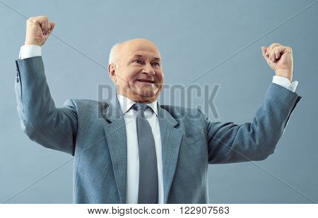Getting the success. Shot of old happy man making a winning gesture and smiling joyfully.