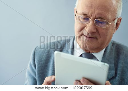 Business plan. Close up shot of wise old man holding tablet and looking thoughtful isolated in grey background.